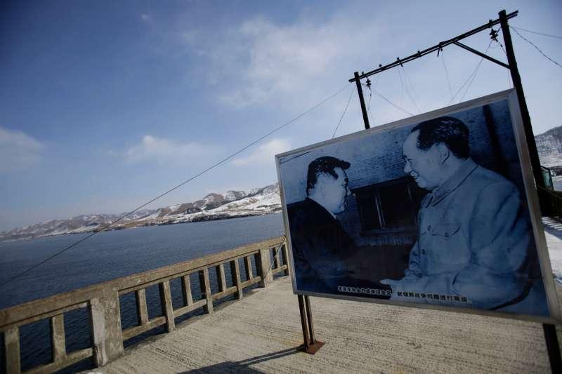韓戰70周年,中國與北韓邊界的毛澤東(右)與金日成會面海報(AP)
