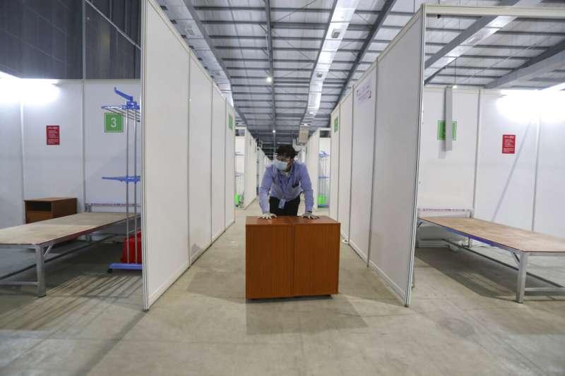 一名志工在緬甸仰光設立的新冠肺炎患者醫療中心裡工作。(美聯社)