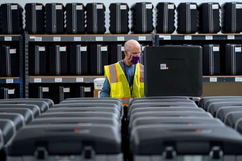 北卡羅來納州的一名工作人員為即將到來的選舉準備讀取選票的機器。(美國之音)