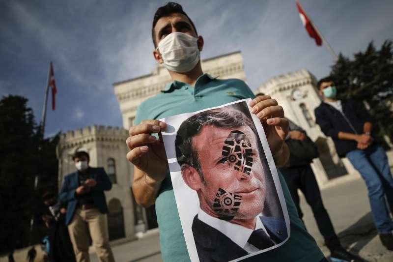 10月25日,土耳其伊斯坦堡一位示威民眾拿著臉上帶有腳印的法國總統馬克宏照片,表達對馬克宏的不滿(美聯社)