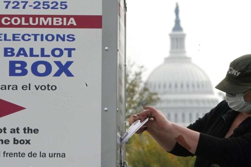 一位美國選民10月28日在國會大廈附近的投票箱完成提早投票。(美聯社)