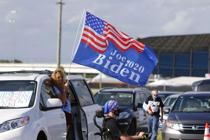 美國佛羅里達州的拜登支持者在造勢活動上高舉支持旗幟。(美聯社)