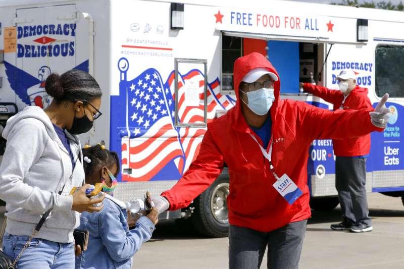 一位工作人員正向提早投票的德州選民發送飲水與點心。(美聯社)