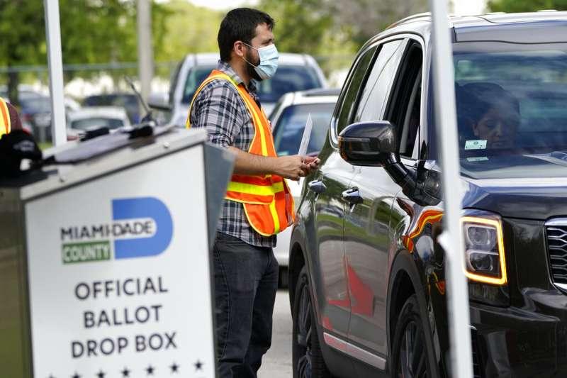 一位佛羅里達州的選務人員正在協助民眾完成投票。(美聯社)