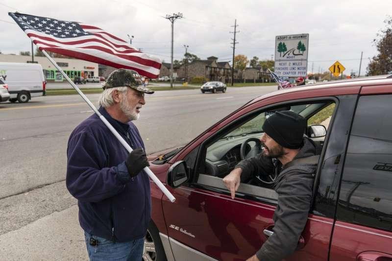 密西根州芒特克萊門斯 (Mount Clemens)一處十字路口的爭吵。路過的駕駛與路旁揮舞國旗的川普支持者互嗆。(美聯社)