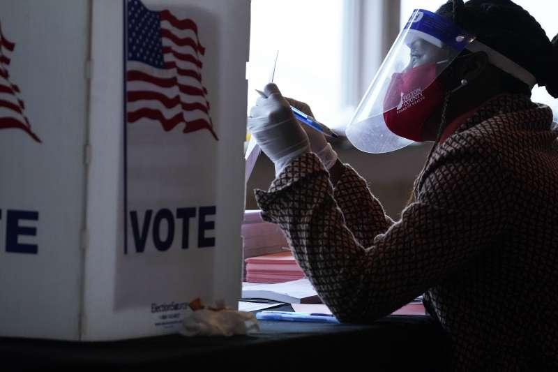 2020年11月3日美國大選投票日,穿戴防疫裝備的選務人員(AP)
