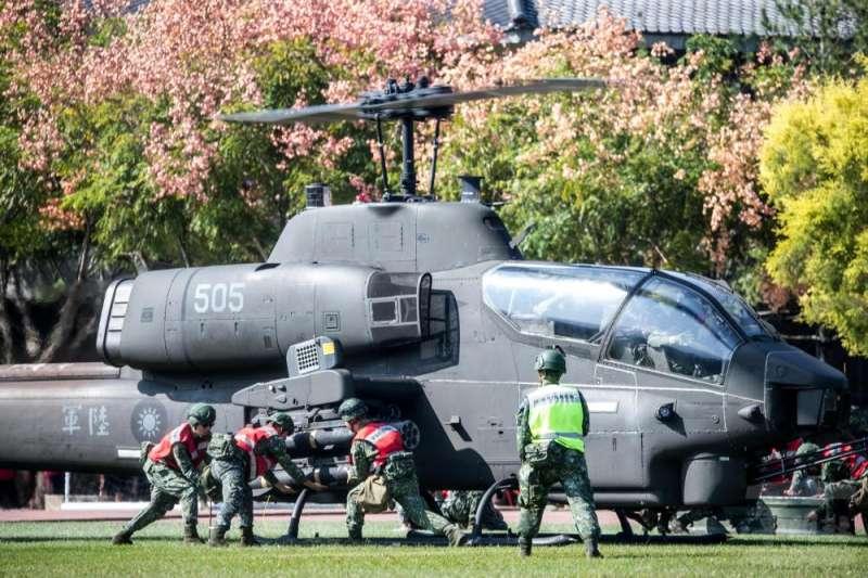 20201105-AH-1W攻擊直升機掛彈同時,座艙內飛官雙手高舉貼窗,避免誤觸電門。(取自軍聞社)