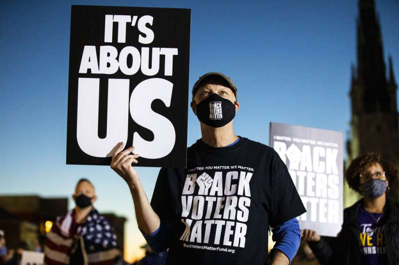 賓州哈里斯堡一名抗議者4日在街頭舉牌,抗議川普要求停止計票的說法。手上的牌子寫著「此事關乎美國」。(美聯社)