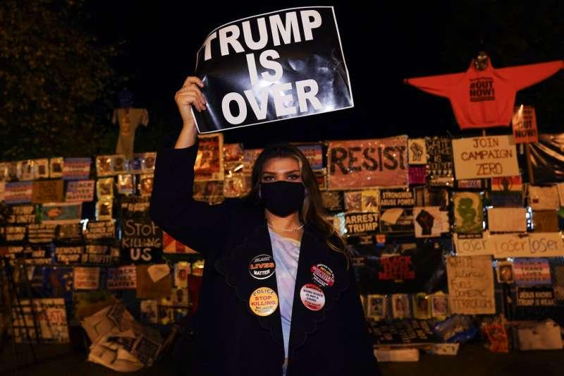 一位華府居民4日在街頭對美國總統要求停止計票的說法表達不滿,手上的標語寫著「川普完蛋了」。(美聯社)