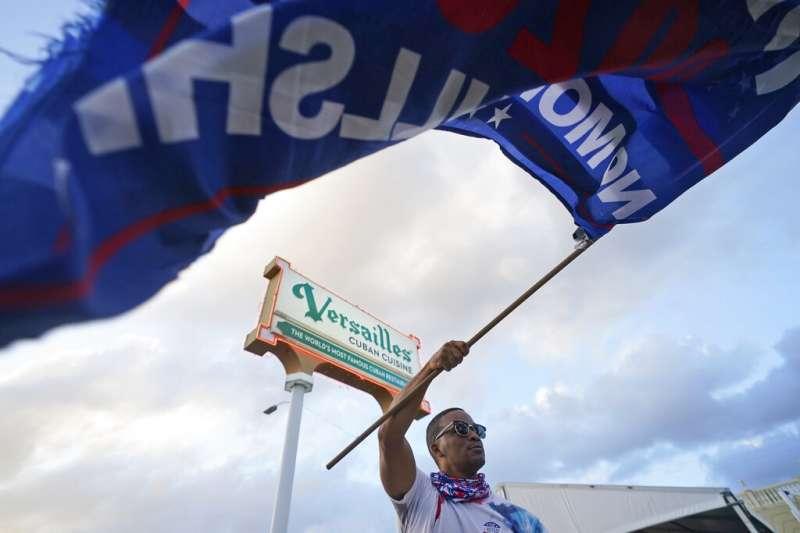川普在佛羅里達邁阿密的支持者4日在一間古巴餐廳外揮舞競選旗幟。 (美聯社)