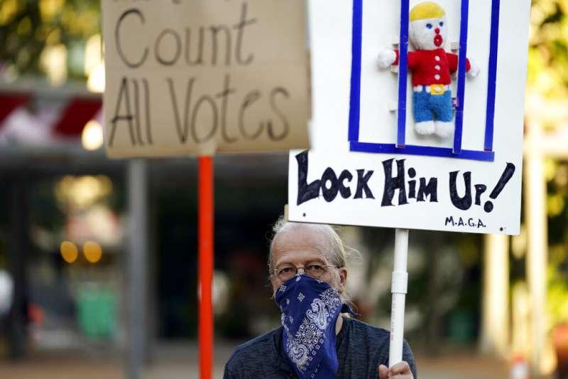 一位德州聖安東尼奧的居民4日上街反對川普「停止計票」的要求,並且要求把他關起來。(美聯社)