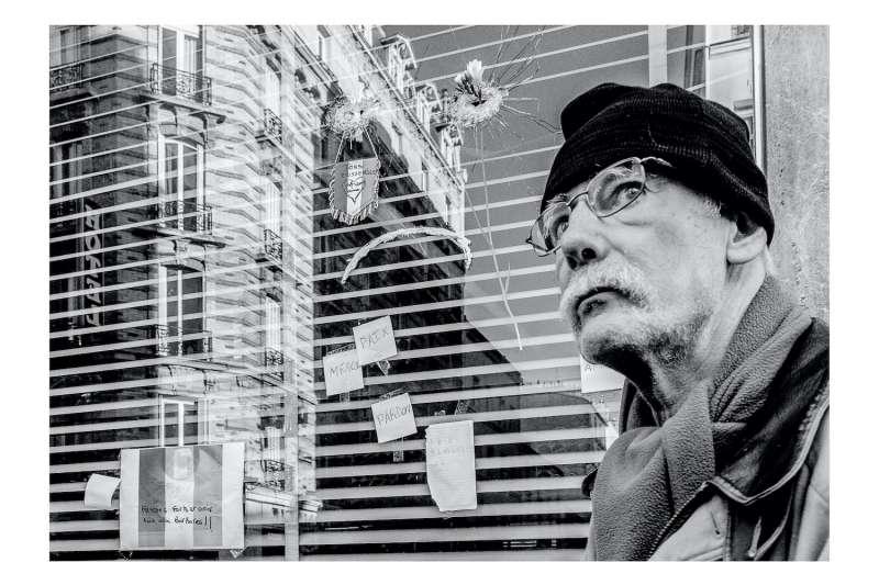 案發現場的玻璃窗留下明顯彈痕,民眾表情茫然。(張家綺提供)