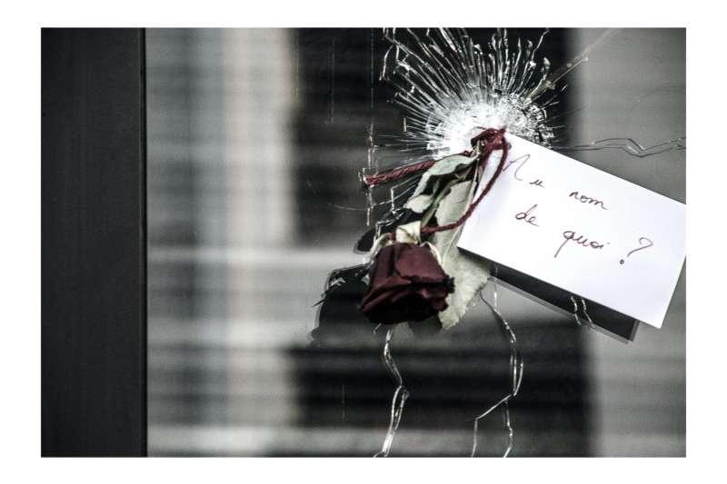 咖啡館玻璃窗的彈孔上插了一朵鮮花,紙條上寫著「為何屠殺?」(張家綺提供)