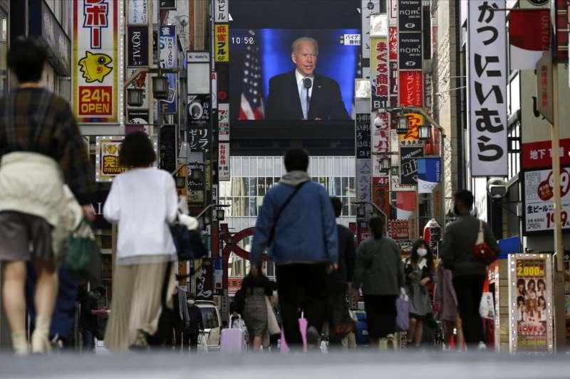 拜登在美國總統大選中勝出後,日本民眾也在東京街頭閱讀快報。(美聯社)