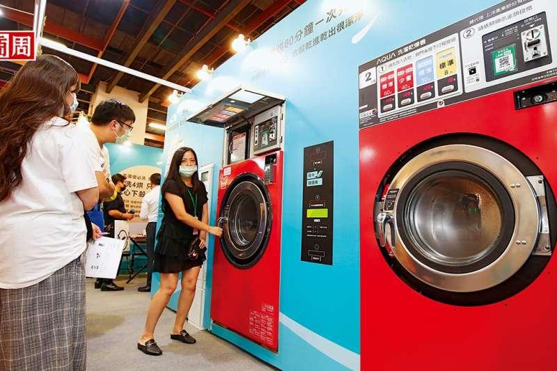 10月台北國際加盟展中,自助洗衣店加盟總部員工,正向加盟主說明洗脫烘三合一的洗衣設備優勢。(圖片來源/商業周刊)