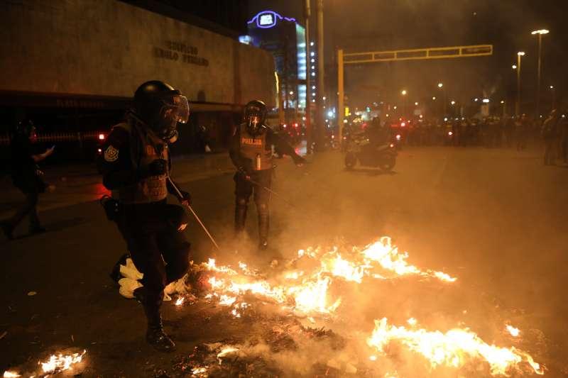 11月12日,秘魯首都利馬,警方正撲滅示威者在最高法院外放的火(美聯社)
