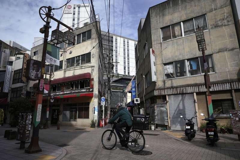 東京淺草區一名送貨人員正戴著口罩工作。(美聯社)