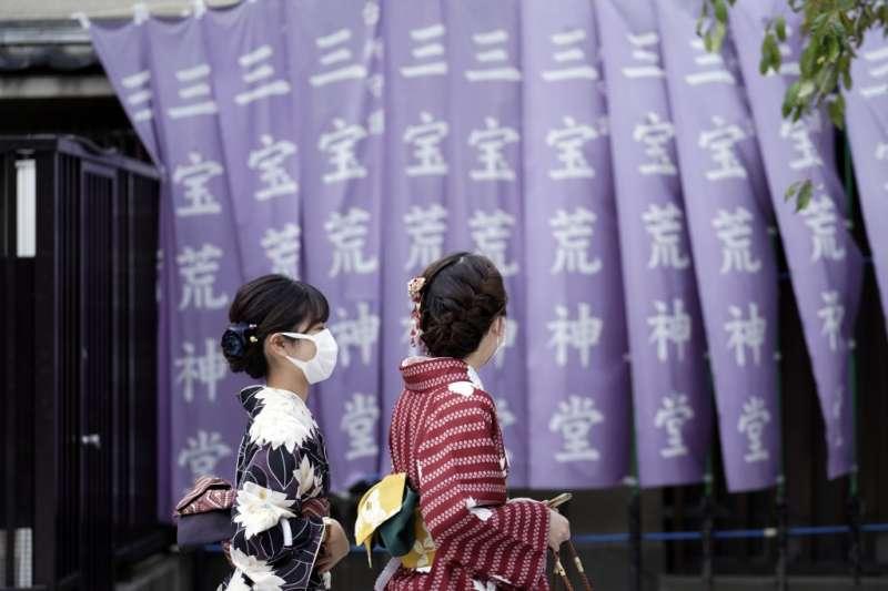 日本疫情升高,東京淺草區的往來行人都戴著口罩。(美聯社)