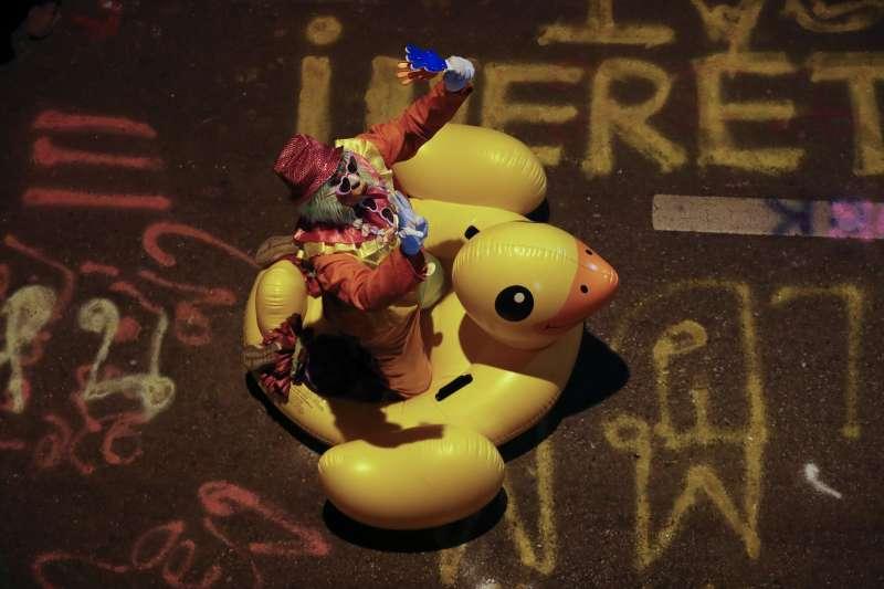 泰國警方17日發射水砲驅離示威者,因此曼谷一名示威者18日帶著黃色小鴨上街以備不時之需(美聯社)