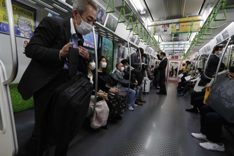 日本新冠疫情進入11月之後急遽升高,東京地鐵乘客也都戴著口罩防疫。(美聯社)