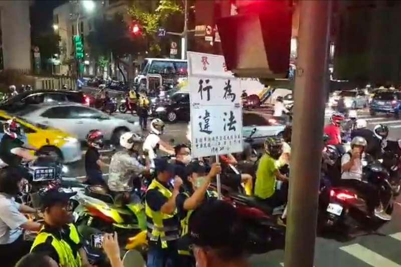 台灣機車權益促進會將於今(20)日晚間6點再次舉行「待轉大富翁」抗議行動。圖為8月「待轉大富翁」抗議行動,警方舉牌驅離民眾。(取自台灣機車權益促進會粉專)