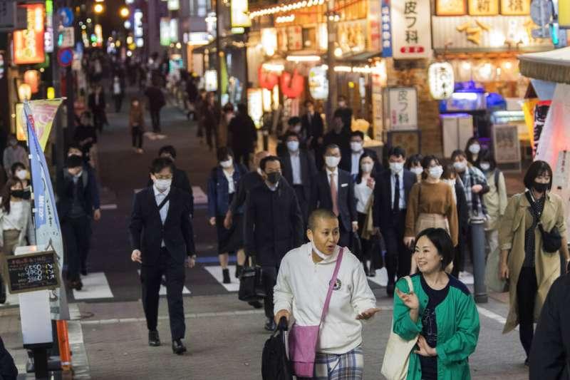 2020年11月19日,東京鬧區街頭的行人有些戴著口罩、但也有人沒戴。(美聯社)