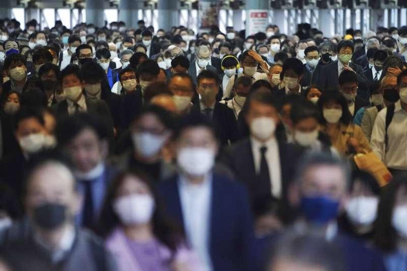 日本疫情急遽惡化,東京地鐵旅客幾乎都戴上口罩。(美聯社)