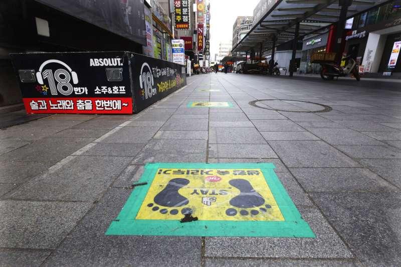 首爾鬧區街頭地面上的「保持社交距離」標記。(美聯社)
