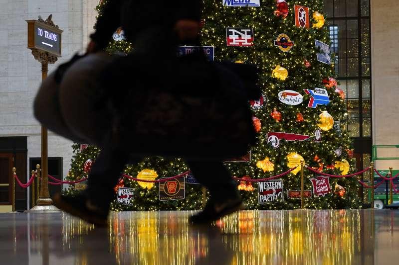 2020年11月25日,一名趕搭火車的旅人在感恩節前一天經過芝加哥車站的聖誕樹前。 (美聯社)