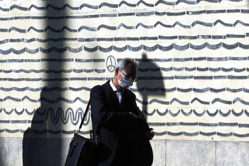 日本疫情近日不斷升高,東京街頭的行人也大多戴著口罩防疫。(美聯社)