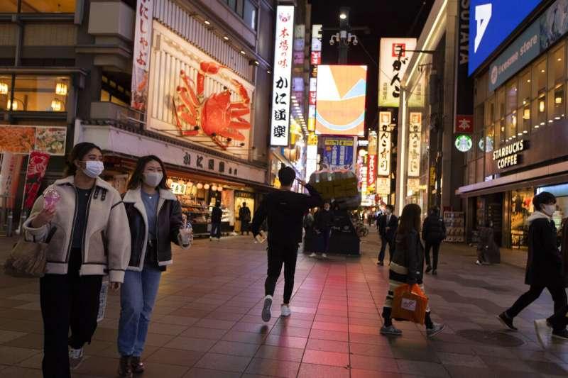 日本疫情近日不斷升高,大阪鬧區的來往行人大多戴上口罩防疫。(美聯社)