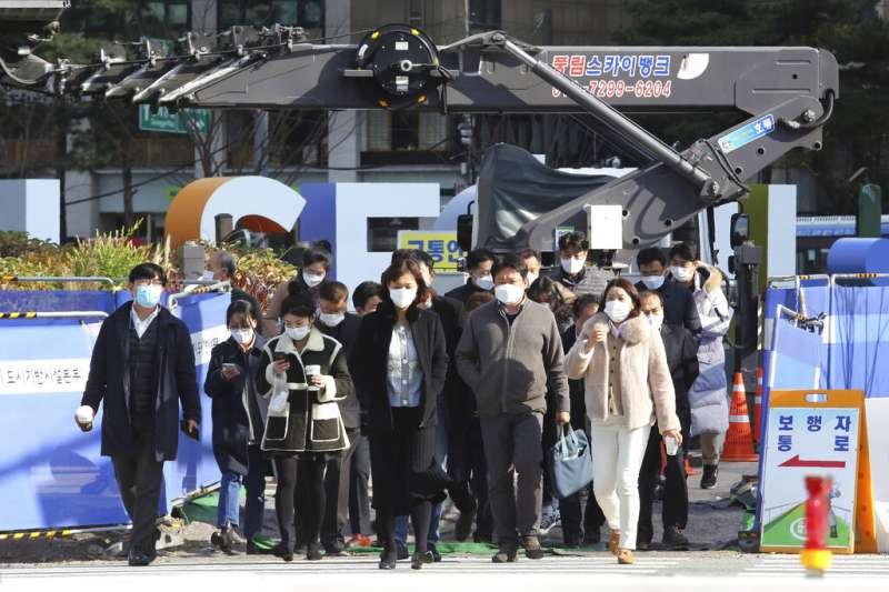 南韓疫情近日不斷升高,首爾街頭的行人大多戴著口罩防疫。(美聯社)