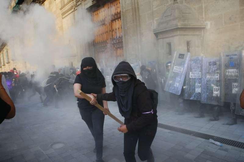 11月25日「國際消除對女性施暴日」,墨西哥女權團體走上街頭、拾起武器抗議。(AP)