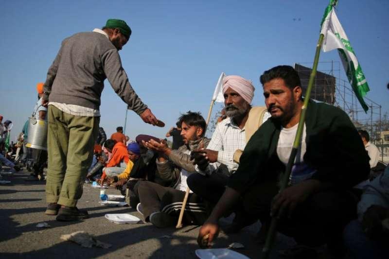 一名印度農民2020年11月28日向參與示威的農民夥伴分發食物。(美聯社)