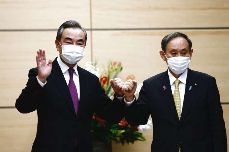 中國外交部長王毅(左)訪日會晤日本首相菅義偉(右),談釣魚台糾紛與CPTPP加入等事宜。(美聯社)