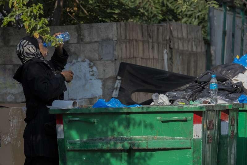 一年多來,黎巴嫩歷經經濟危機、新冠疫情與貝魯特大爆炸,經濟慘不忍睹,圖為貝魯特街友在垃圾桶撿拾飲水。(AP)