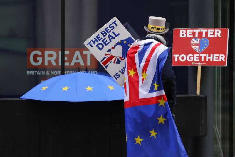 英國脫歐過度期在即,一位倫敦民眾在街頭高舉「反對無協議脫歐」、「英國歐盟在一起更好」的標語。(資料照,美聯社)