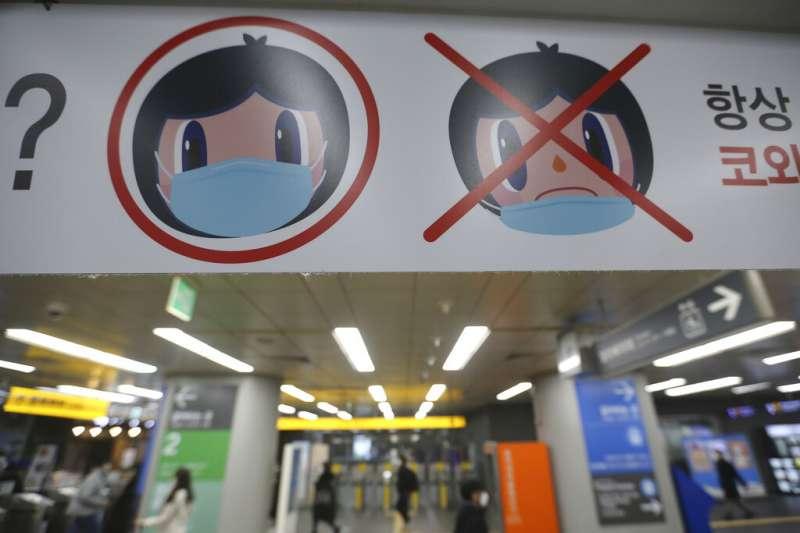 首爾地鐵的佩戴口罩宣導海報。(美聯社)
