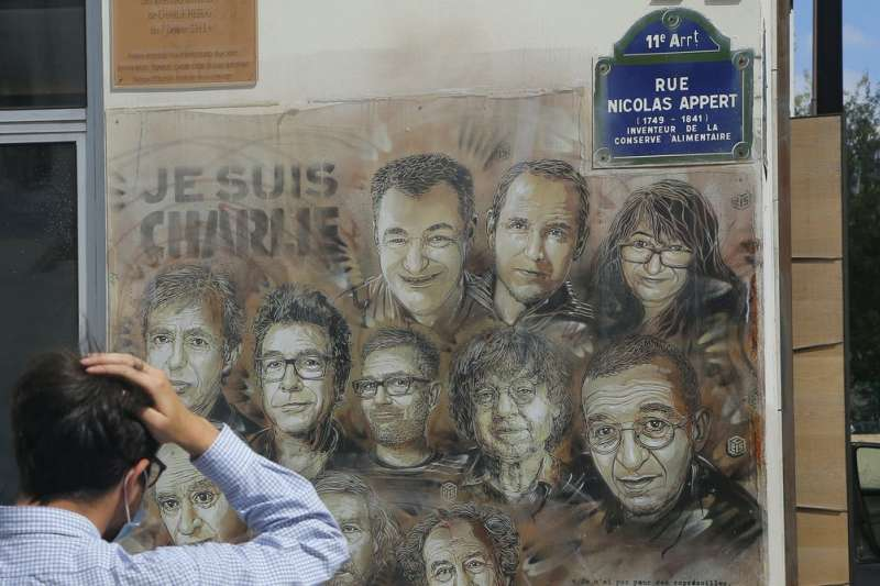 法國街頭藝術家蓋米(Christian Guemy)以繪畫哀悼《查理周刊》槍擊案的罹難者(美聯社)