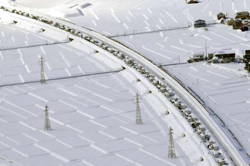 強烈冷氣團導致日本海一側下大雪,新潟、群馬縣境內高速公路16日晚間起受阻,17日竟有上千輛車受困雪中。(美聯社)
