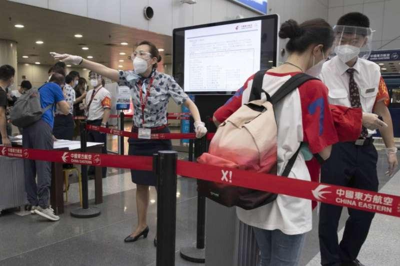 中國北京首都機場的工作人員檢查旅客們的COVID-19測試結果(AP)