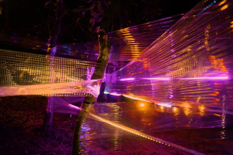 藝術家莊志維作品 《柔軟的纏繞》 將工業生產的薄膜,捆繞於現地樹林之中,搭配照射各色的LED燈,藉由材料的特性創造虛無飄渺的空間感。樹林間或人工或自然地交織糾纏,探討著人與自然環境間的交互關係。(擷取自龍崎光節 - 空山祭粉專)
