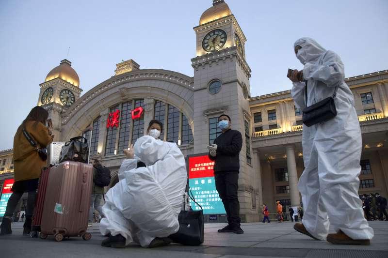 武漢是全球第一個在疫情下封城的城市,去年二月世衛組織就已為新冠肺炎正名。圖為穿著防護衣的人員在漢口車站外加緊消毒。(美聯社)