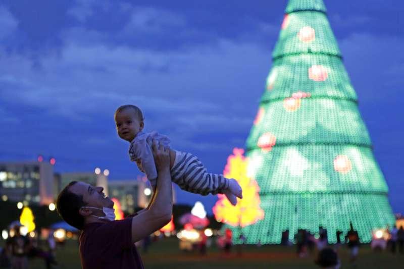 巴西一名父親在巴西利亞的廣場上跟孩子一起玩耍。(美聯社照片/ Eraldo Peres )