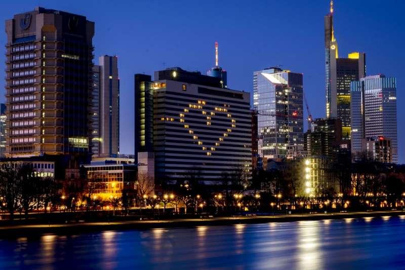 德國新冠疫情升高,法蘭克福萊茵河畔的大樓投射出一顆愛心為世人加油。(美聯社)