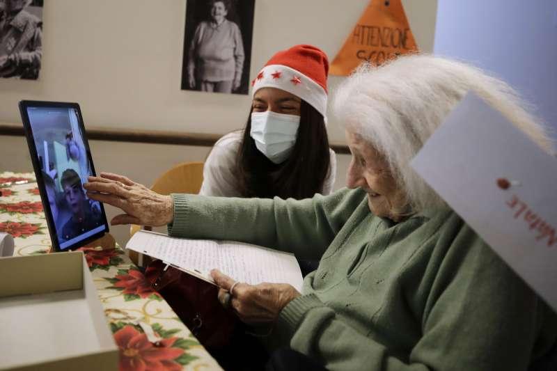 圖為美國養老院的老人家與自願者互動。(AP)