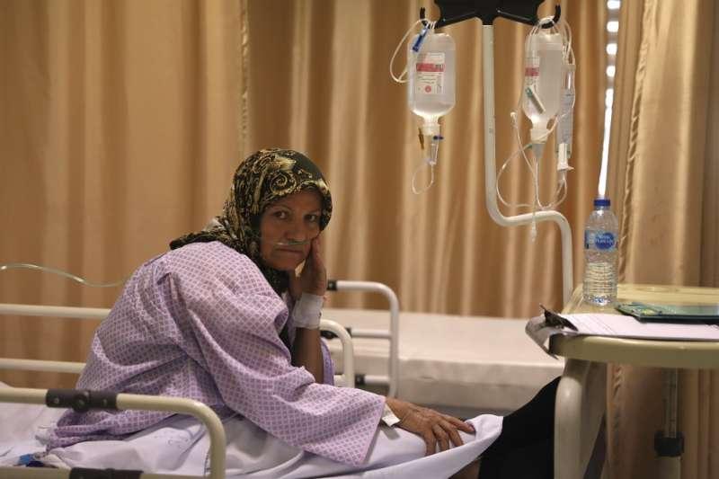 伊朗的新冠疫情嚴重,首都德黑蘭醫院裡的一名新冠肺炎病患正坐在床上(美聯社)