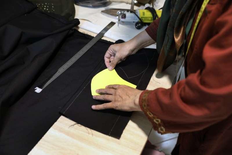 婦女團體「信仰」裡的哈什米安正在裁布,準備製作布口罩(美聯社)