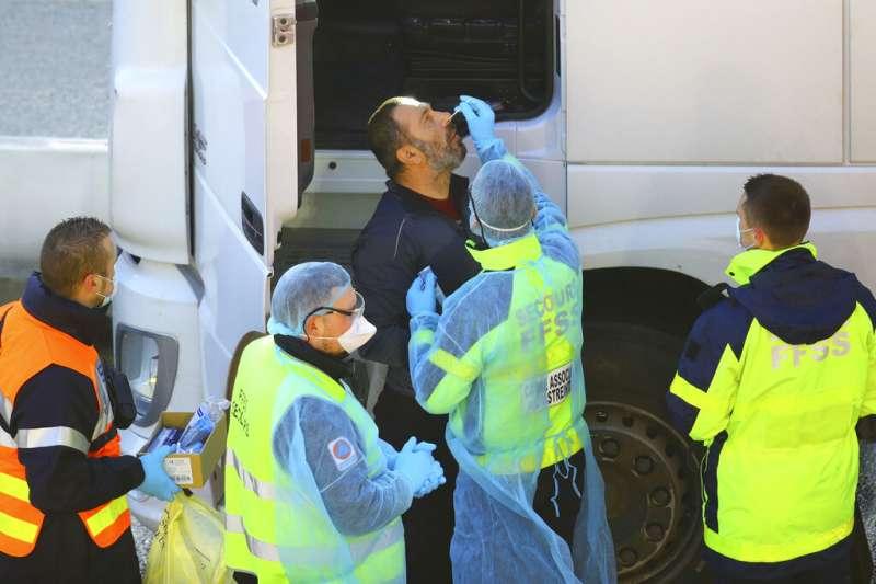 一名貨車駕駛在英格蘭肯特郡的多佛港接受新冠病毒篩檢,英國變種新冠病毒(B.1.1.7)的出現,使得英國邊境成為敏感的重點防疫地帶。(美聯社)