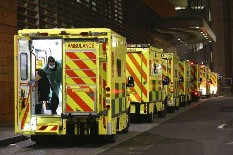 皇家倫敦醫院外停放了一整排救護車。由於英國疫情快速嚴重惡化,英國政府正在考慮宣布更嚴格的疫情對策。(美聯社)